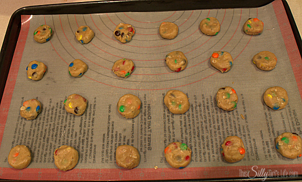 Using a teaspoon sized scoop or spoon, scoop out the cookies and roll into a ball. Flatten the tops of the cookies so they spread evenly, add more m&ms on top for looks if desired.